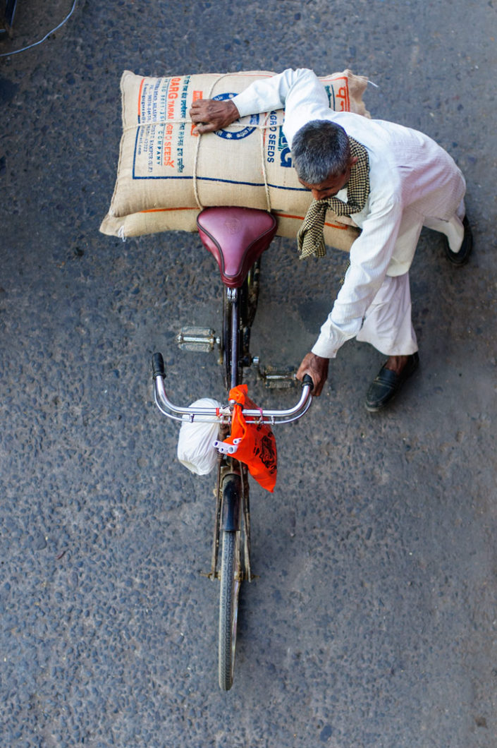 An elderly man pushes his overloaded bicycle in North India.