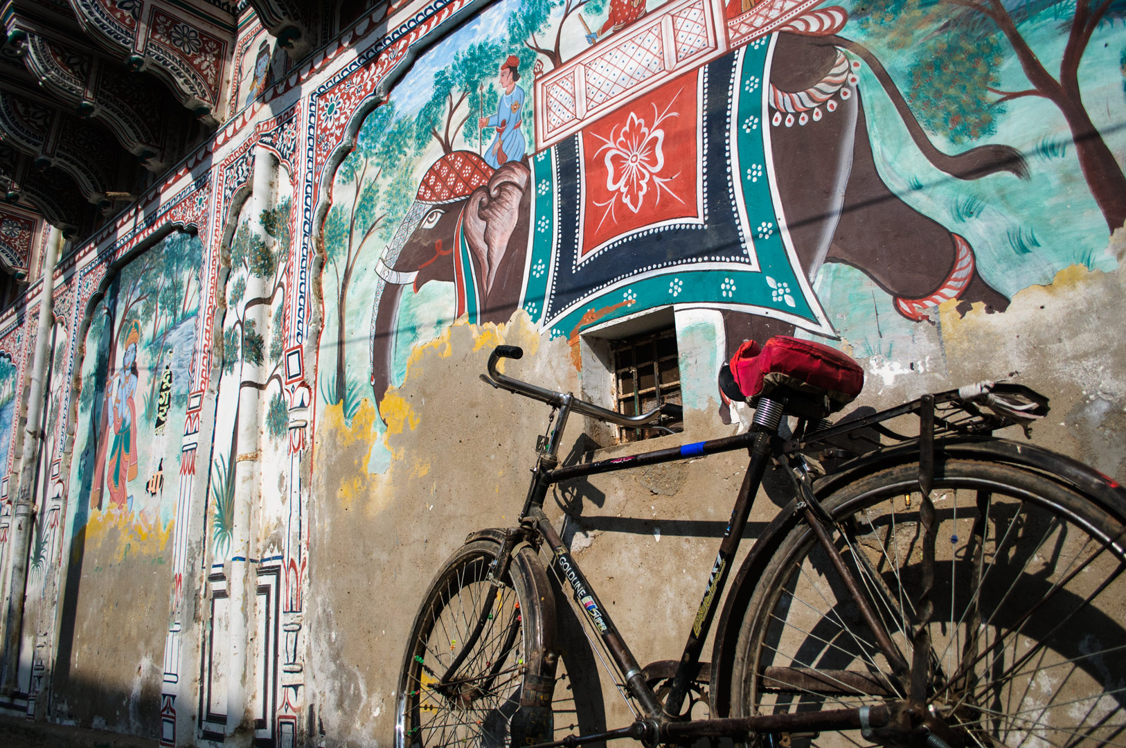 An Indian bike leans against a painted wall in the Shekhawati region of North India.
