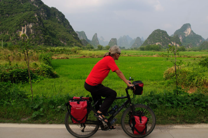 A touring cyclist pedals through the karst mountains near Yangshuo, China.