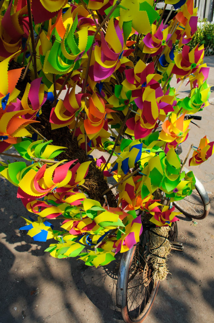 Pinwheels are piled on top of a bicycle in Vientiane, Laos