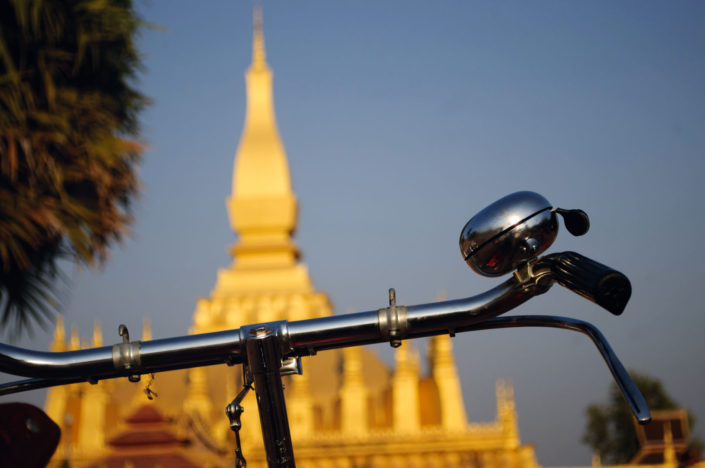 A bicycle stands in front of the temple in Vientiane, Laos