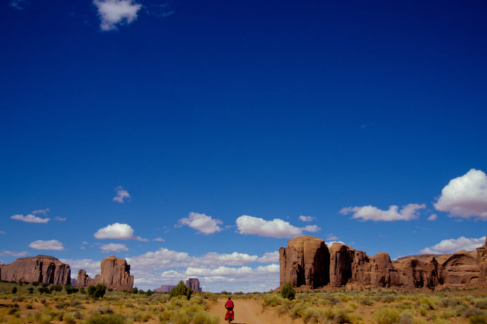 A little red cyclist heads into monument valley.