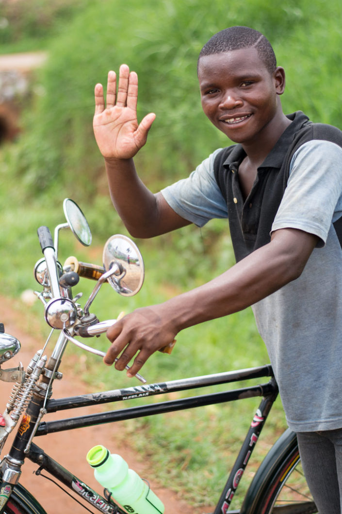 A Malawi bicycle taxi chauffeur waves his hand