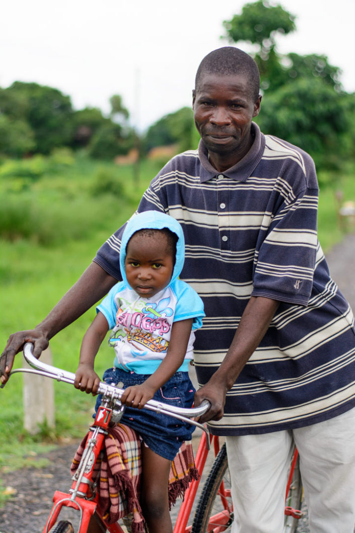 A Malawi father holds his bicycle while his daughter sits on the front tube.