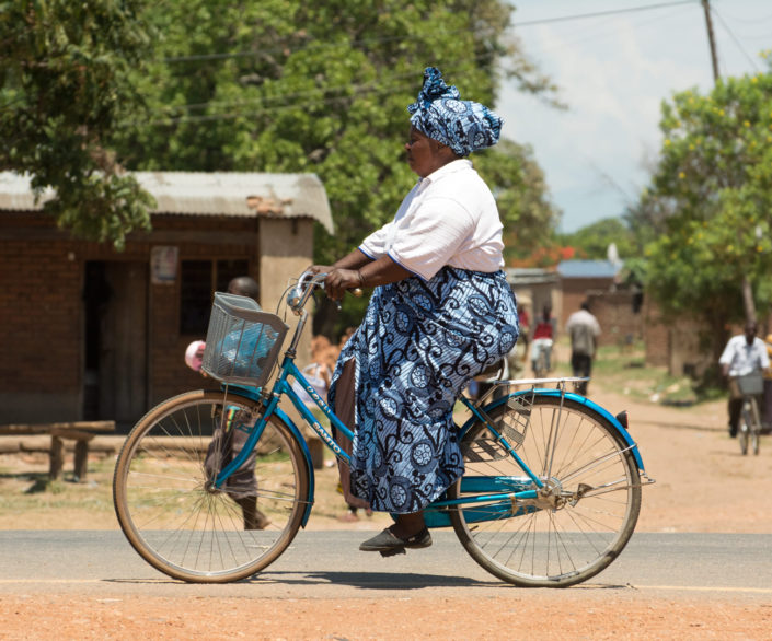 A Malawi woman cycles home from the market