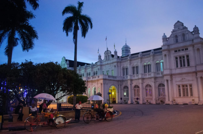 Penang city hall with rickshaws parked in front.