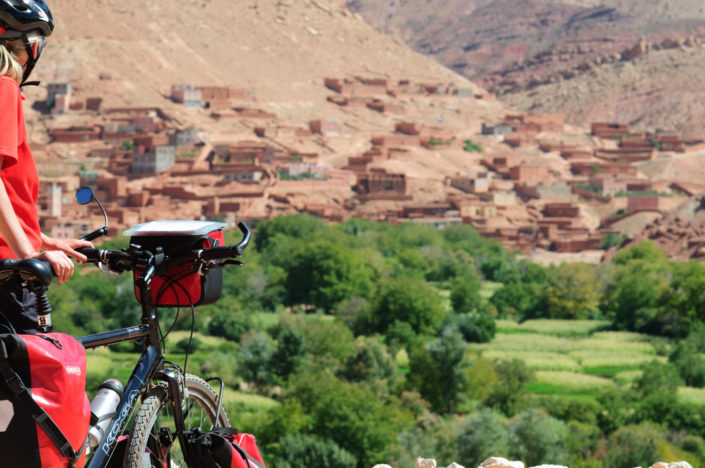 A touring cyclist looks out over a village in Morocco