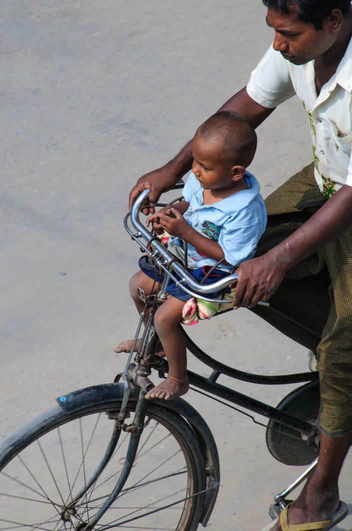 A father transports his son by bicycle in Myanmar