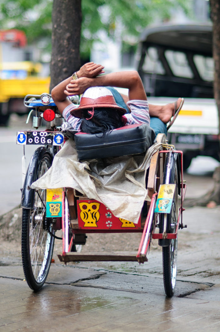 A rickshaw chauffeur takes a nap in his rickshaw in Myanmar.