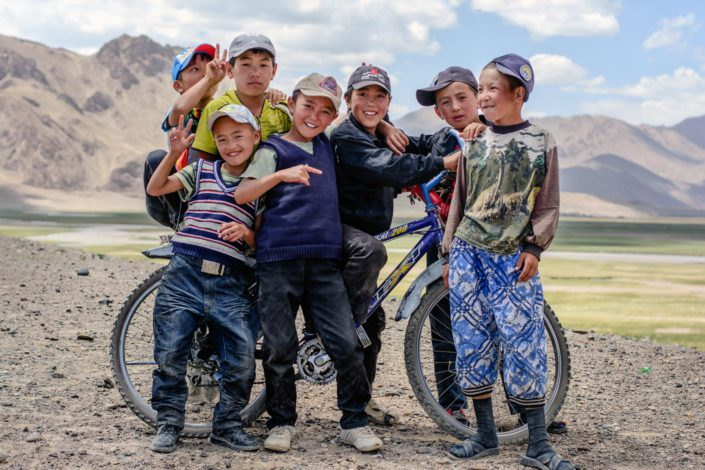Tajikistan boys stand in front of a bicycle.