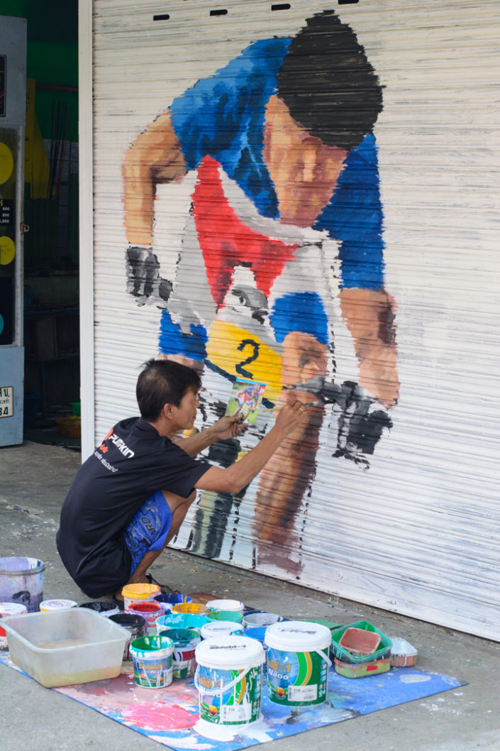 A Thai mand paints a bicycle on a garage door in Thailand