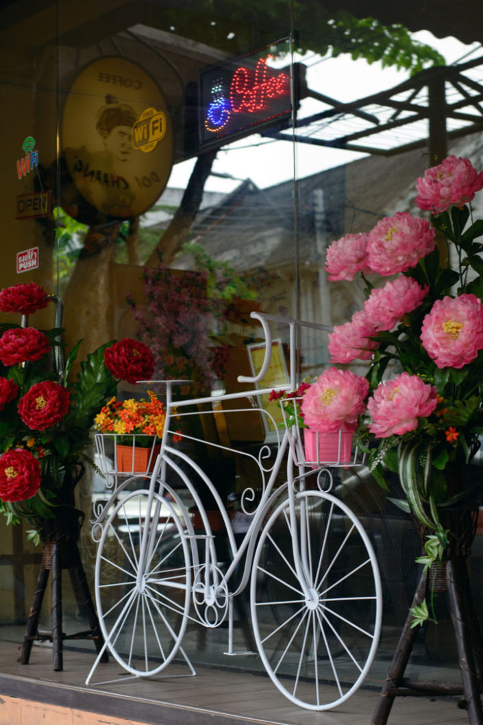 A white bicycle decoraes a store window in Thailand