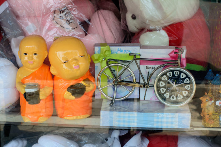 A bicycle clock is for sale in a Thai store window