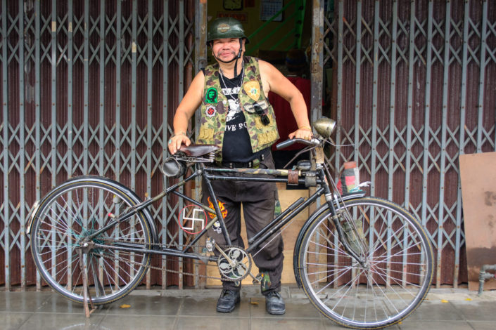 A Bangkok man stands proudly behind his decorated bicycle in Thailand.