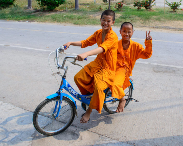 Two young monks ride a bike in Thailand.