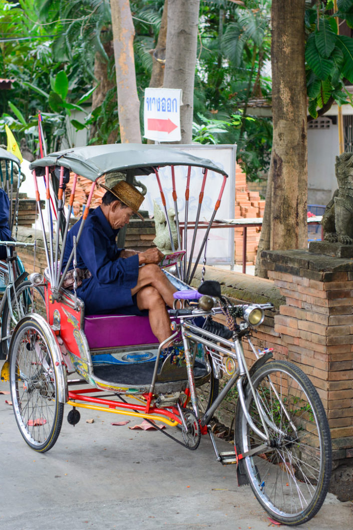 A rickshaw chauffeur waits for passengers in Thailand
