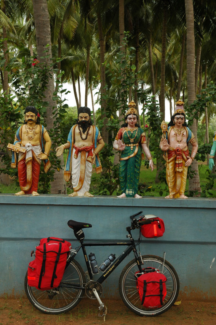 A fully loaded touring bicycle is leaned against a temple wall in South India.