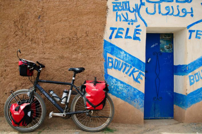 A fully-loaded touring bicycle is leaned against a wall in Morocco