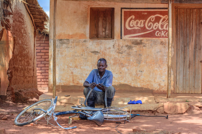 A Zambian man repairs a bicycle flat tire.