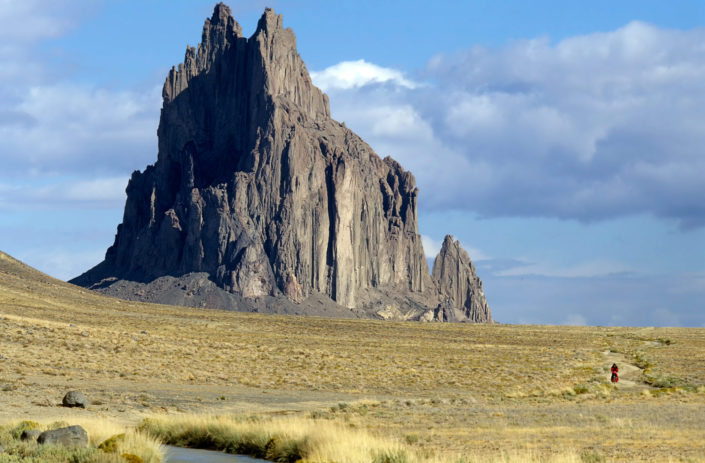 A little red cyclist rides away from Shiprock