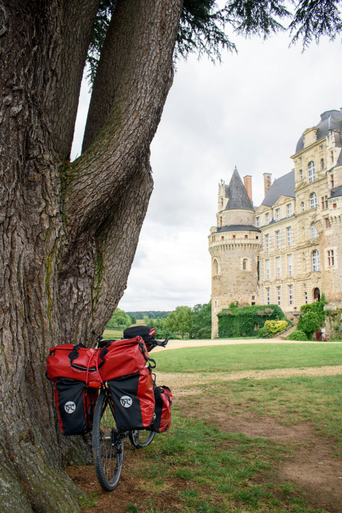 A touring bike leans against a tree with a view over a French castle.