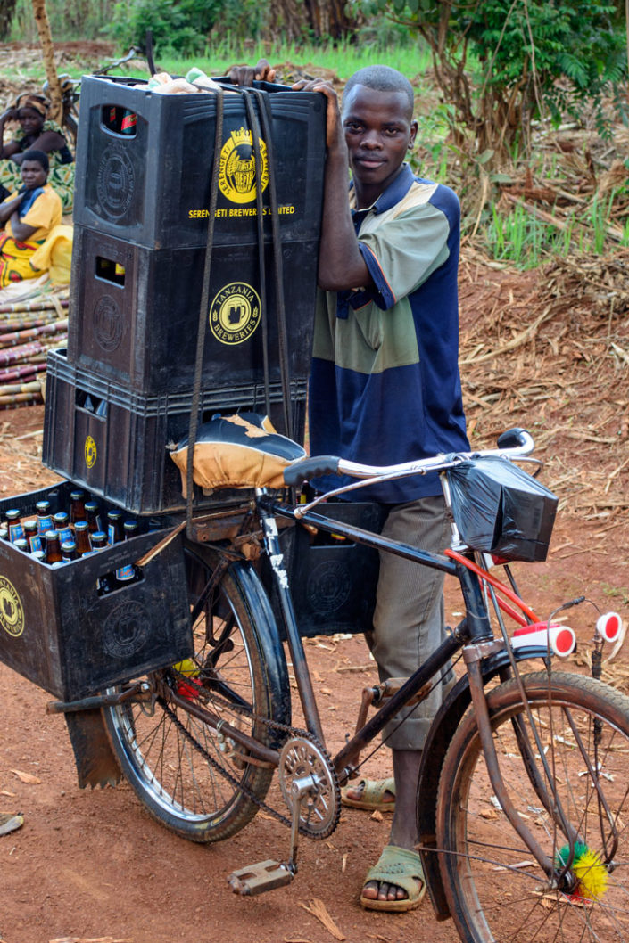 An African stands next to his bicycle that is piled high with crates of beer.