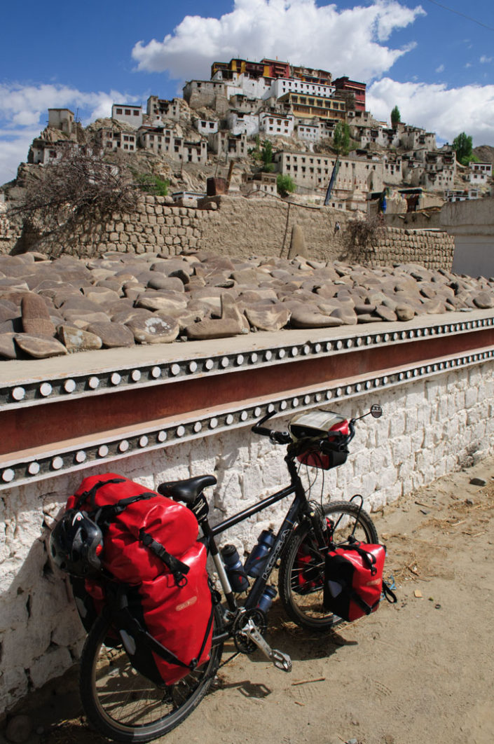 A touring bicycle is leaned against a wall near Thiksey Monastery in North India.