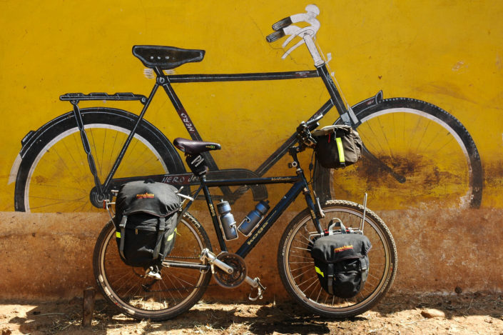 A touring bike is parked against a wall with a mural of an Indian Hero bicycle on it.