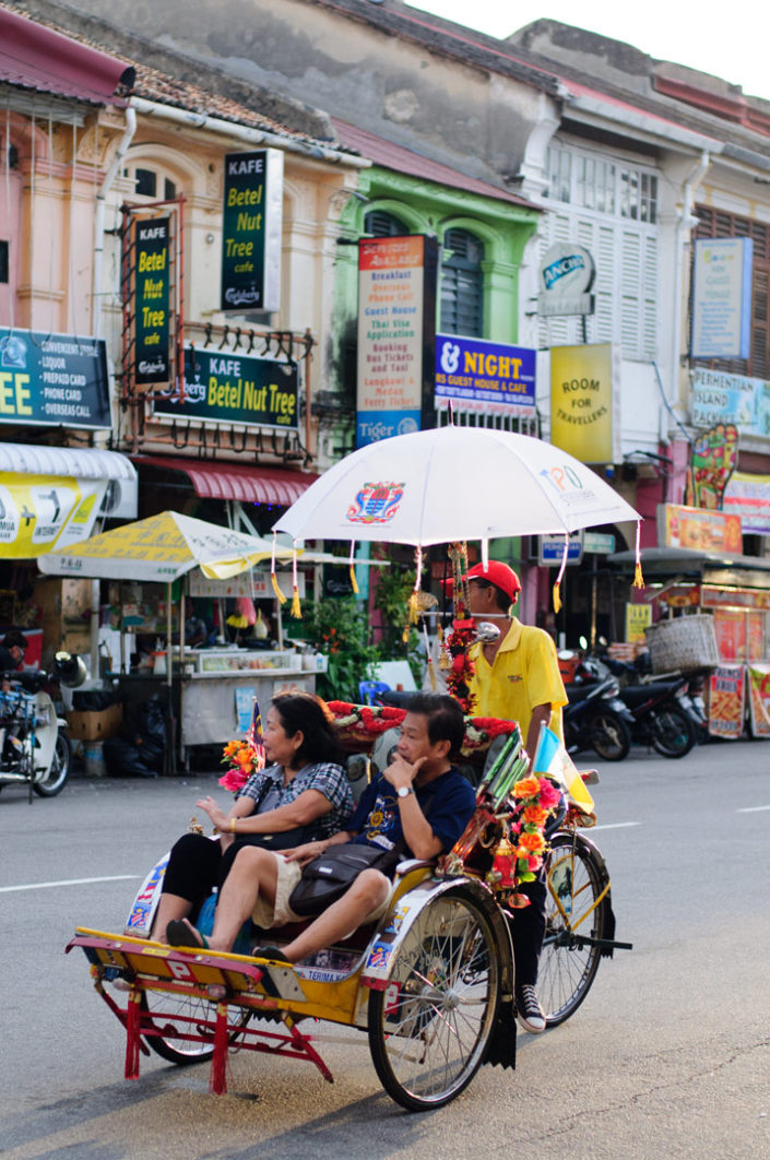Tourists take a rickshaw tour of Penang, Malaysia