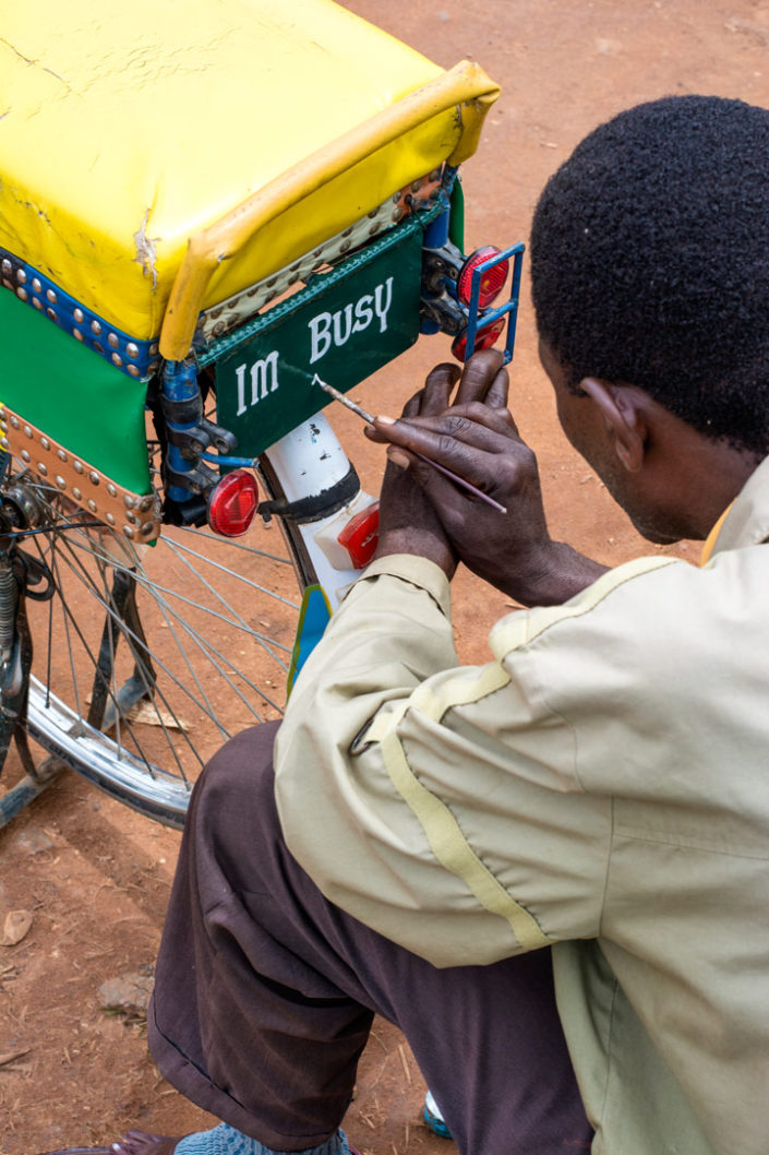 An African man paints text on a bicycle license plate