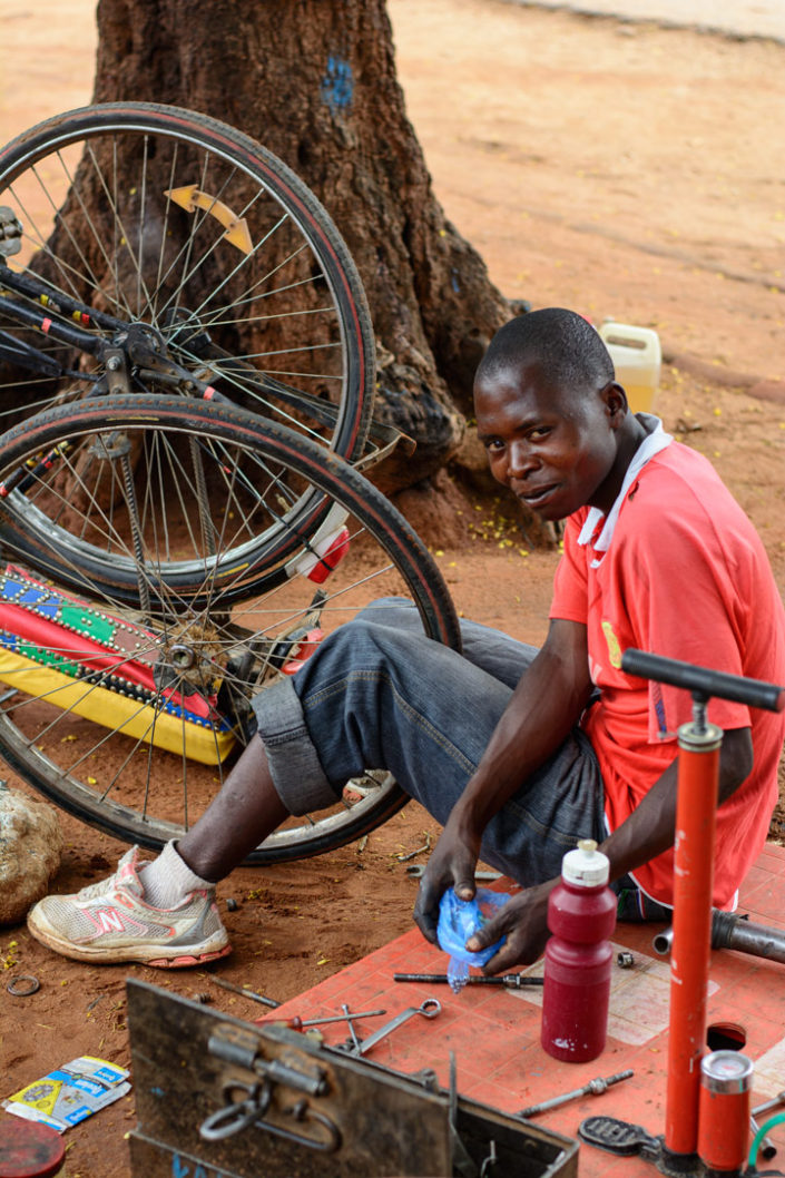An Africna bicycle repair man fixes a bike wheel