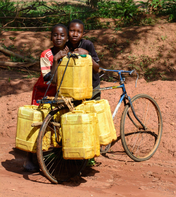 Two African children stand next to a bicycle loaded with water jugs.