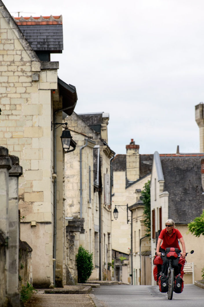 A cyclist rides through a small town in France.