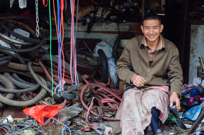 A Chinese man sits in his bicycle repair shop
