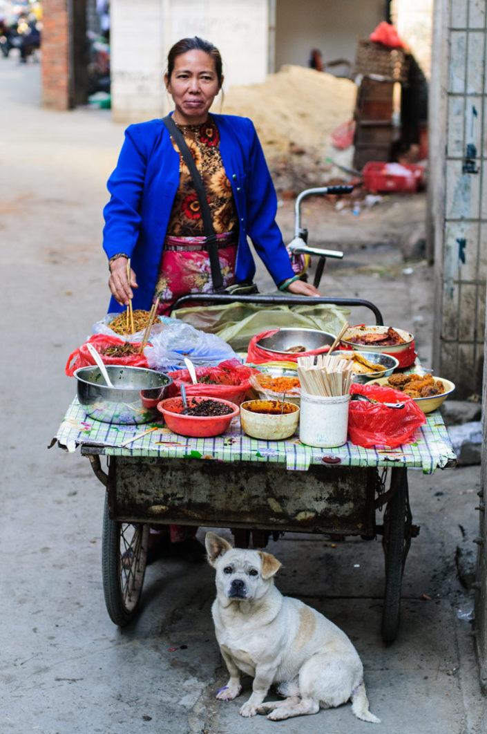 A lady stands behind a cargo bike -food stall in China