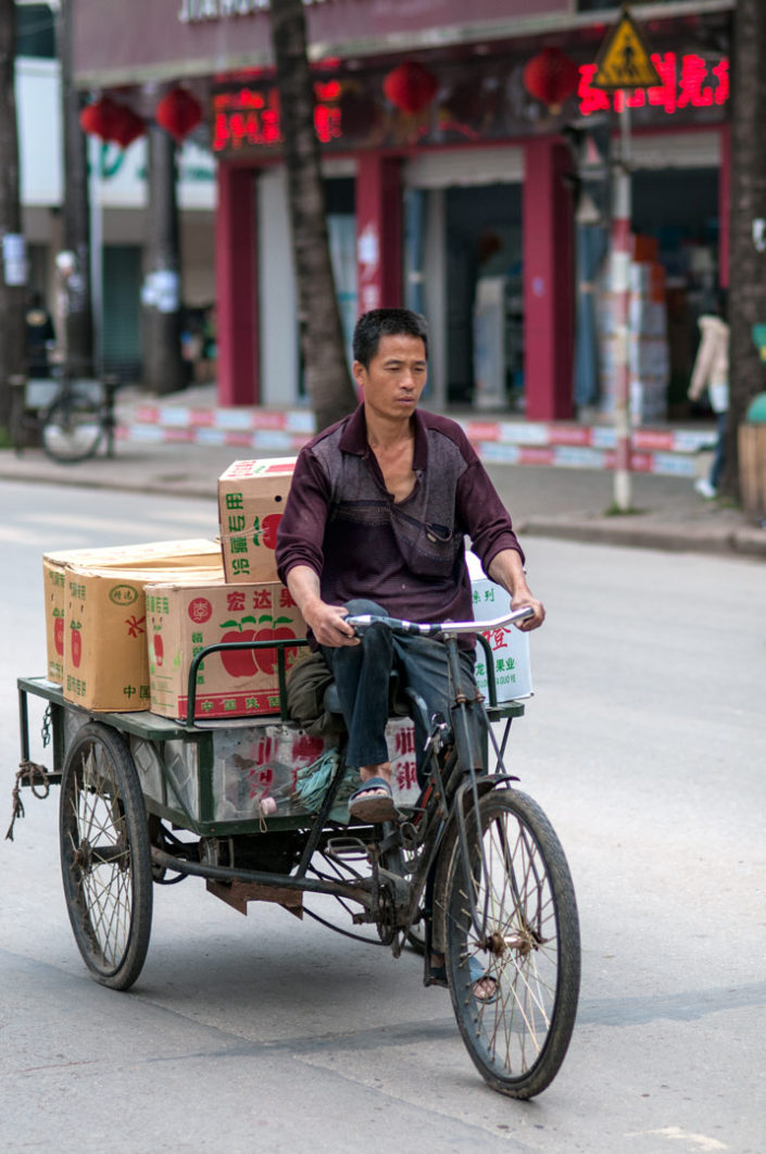 A Chinese man rides a cargo bike