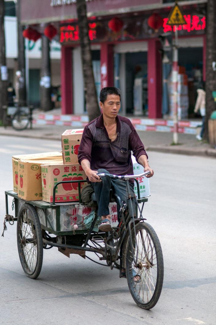A Chinese man rides a cargo bike