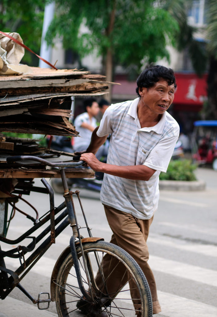 A Chinese man pushes a fully loaded cargo bike in China