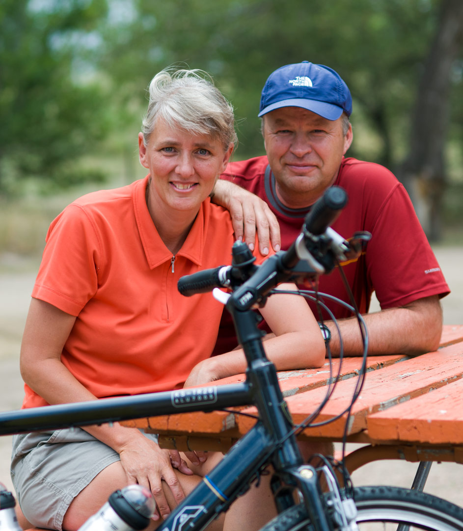 Paul Jeurissen and Grace Johnson sit behind a touring bicycle.
