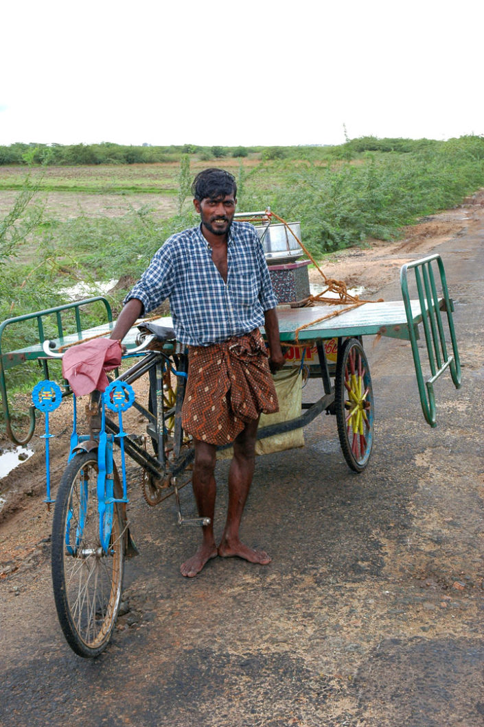 A man stands next to a rickshaw that is loaded up with a metal bed frame in India