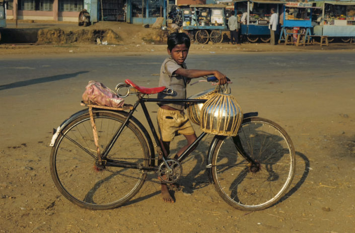 A boy in India holds a bicycle
