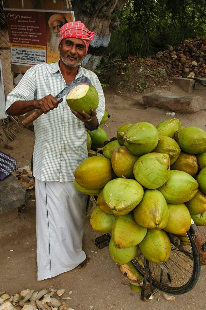 A cycling coconut salesman in India cuts open a coconut