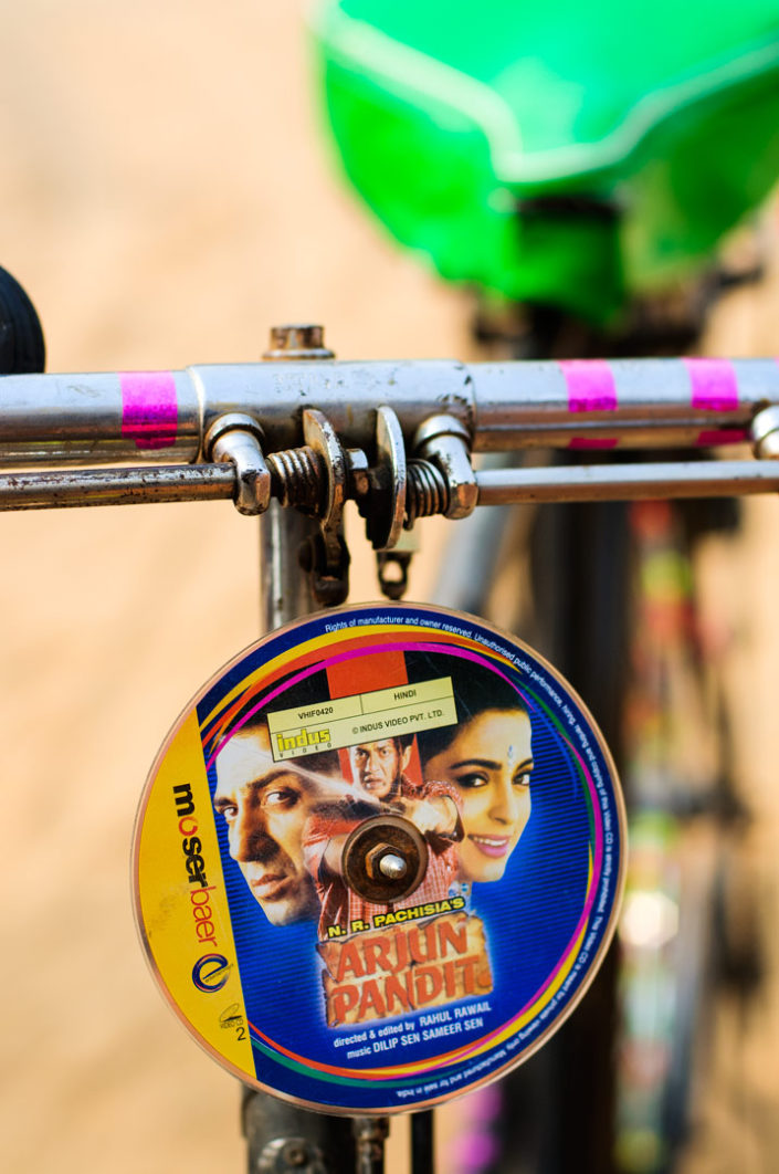 A music cd hangs from bicycle handlebars in India