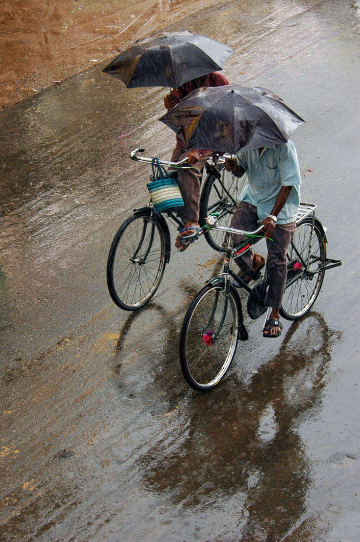Two Indian cyclists pedal while holding umbrellas during monsoon rains