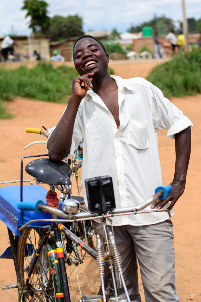 A smiling bicycle taxi chauffer stands next to his bike in Malawi, Africa