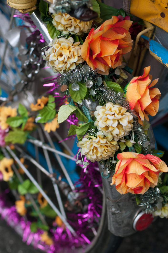 A rickshaw wheel in Penang, Malaysia is decorated with flowers