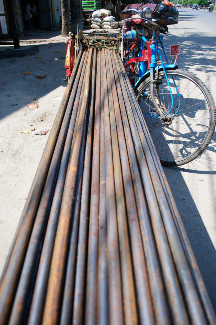 A trishaw is loaded with steel rebar in Myanmar