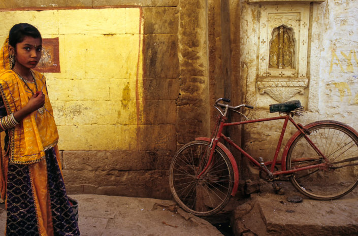 A red bicycle leans against a wall in Jaisalmer, India
