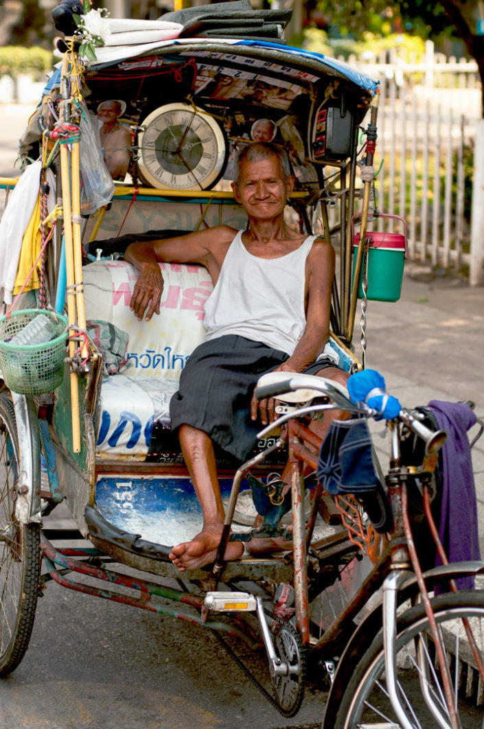 An elderly Rickshaw chauffeur in Thailand waits for a customer