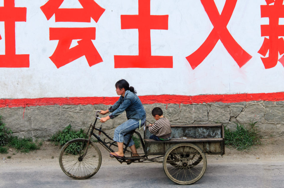 Bicycle culture - A mother and child pedal their cargo bike past a Chinese sign